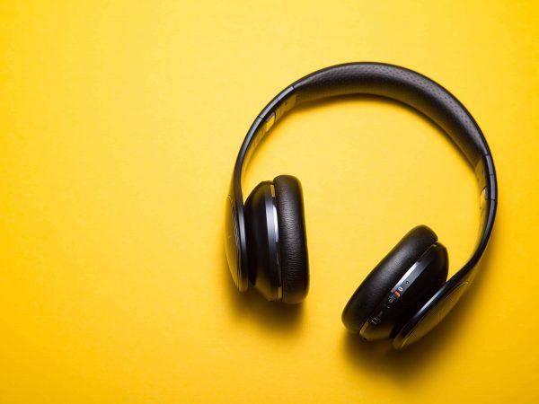 Fone de ouvido sem fio Bluetooth preto com alça para a cabeça sobre fundo amarelo.