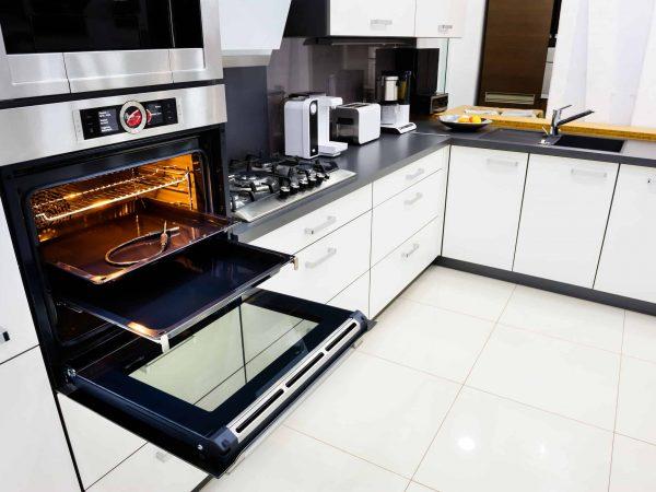 Imagem de cozinha e forno elétrico aberto.