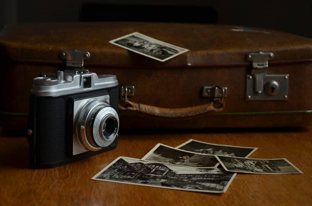 Imagem de algumas fotos impressas com máquina fotográfica ao lado e mala.