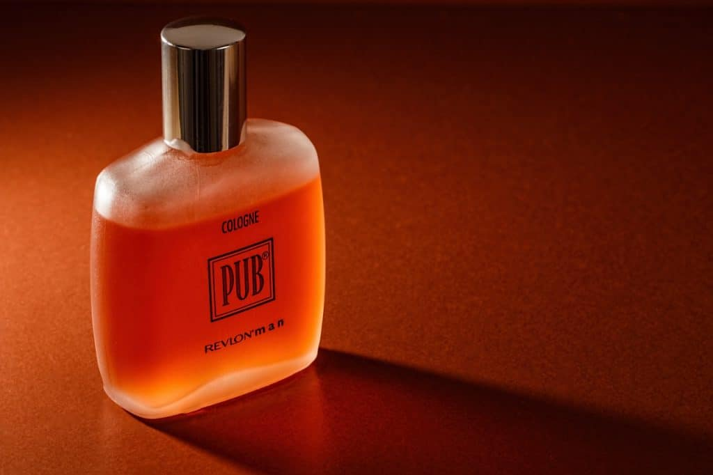 Frasco de perfume masculino laranja sobre mesa.