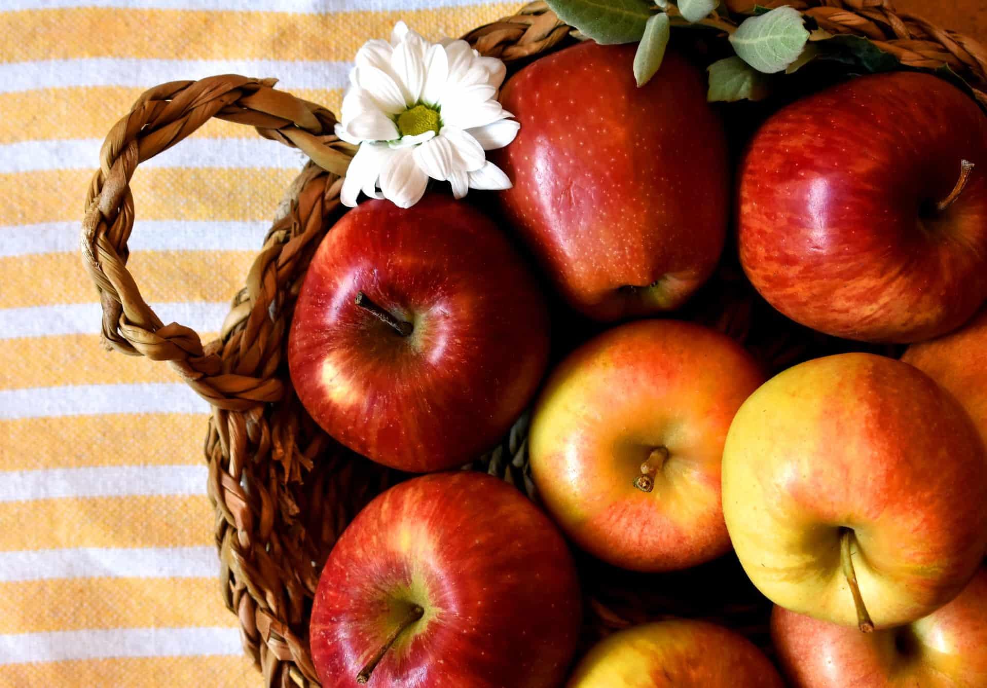 Foto de uma fruteira de palha com maçãs vermelhas e um flor branca tirada de cima.