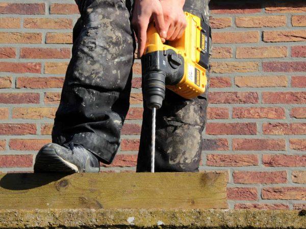 Imagem mostra um homem usando uma furadeira em uma placa de madeira.