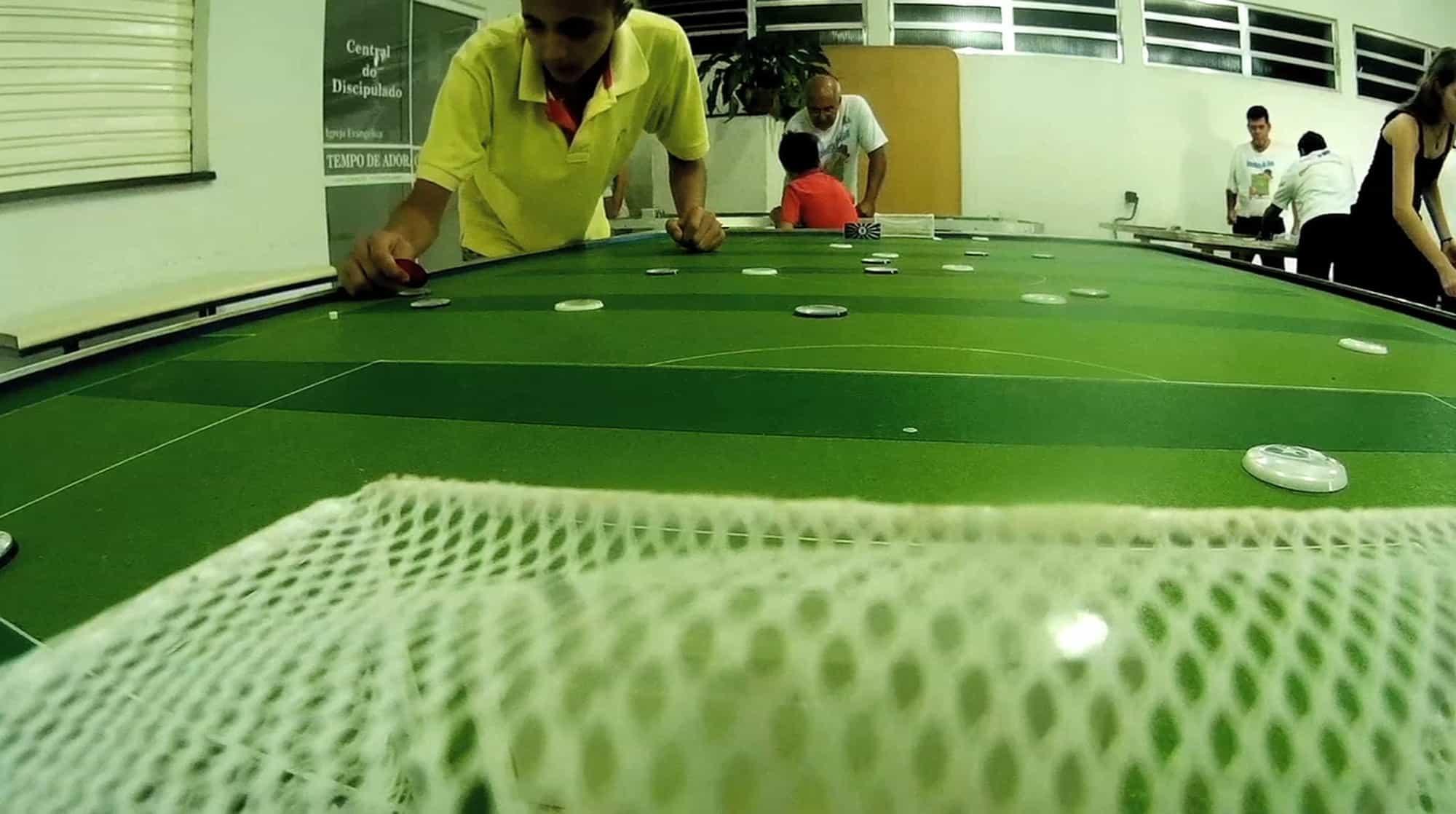 Criança jogando futebol de botão em mesa vista de trás de uma das traves.