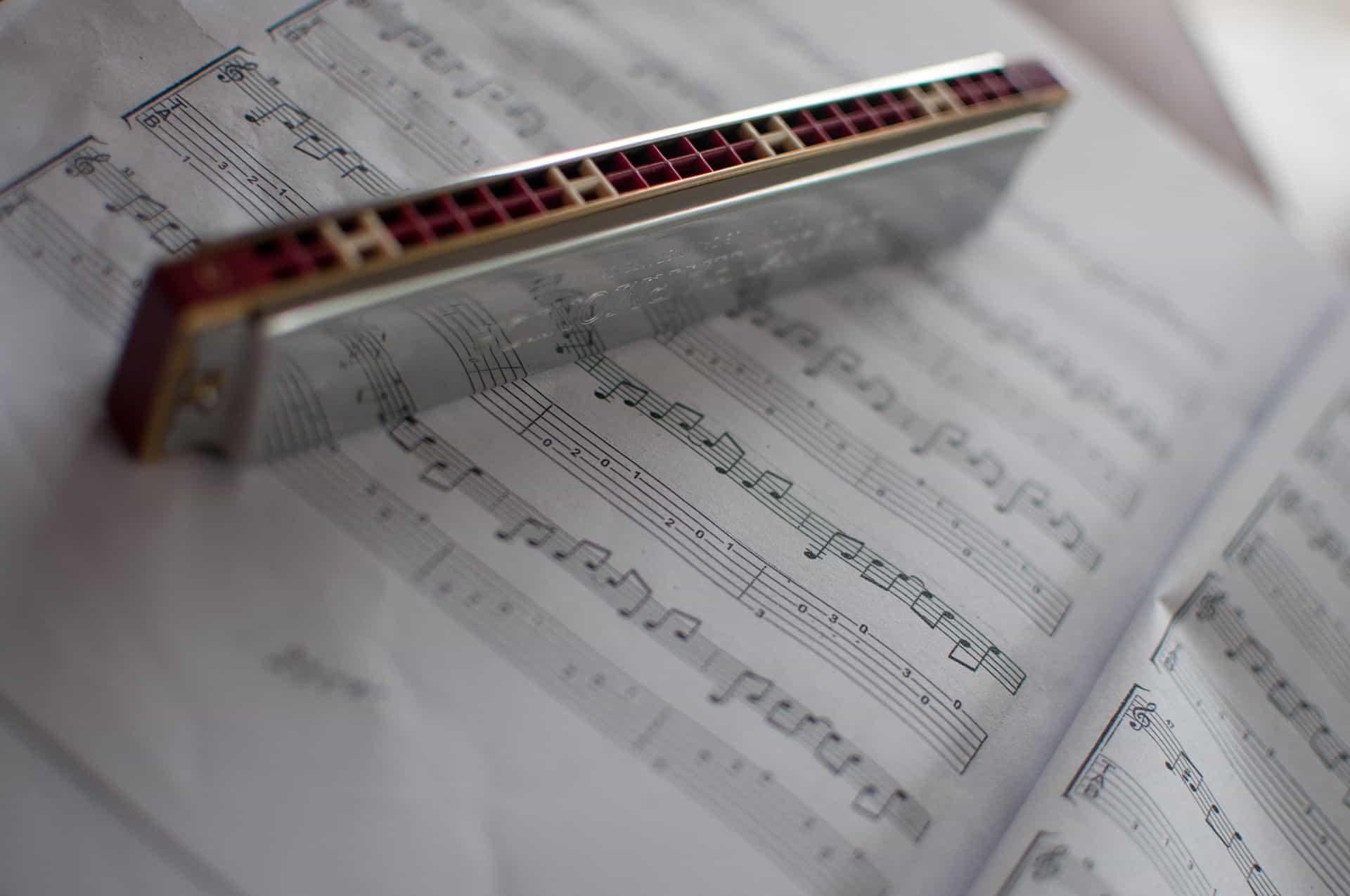 Gaita de boca em cima de um livro de partituras.