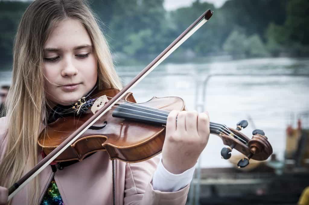 Foto de uma garota tocando violino, prestando atenção nos movimentos do arco; ao fundo, uma paisagem natural, indicando a prática ao ar livre.