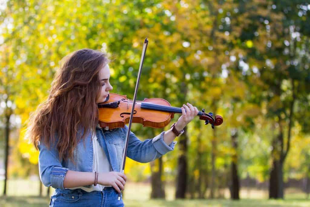 Imagem de uma garota tocando violino em um parque com árvores de folhas amareladas.