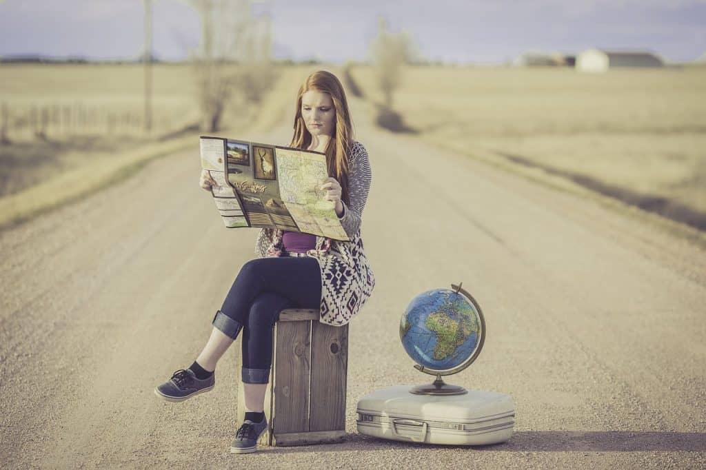 Imagem mostra garota sentada em mala em estrada, segurando um mapa e com globo terrestre ao lado.