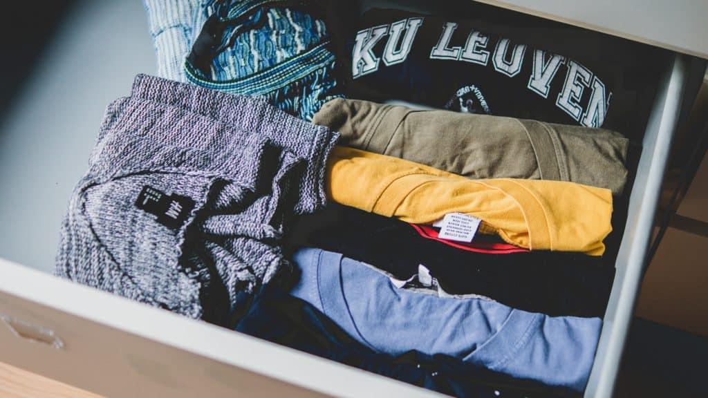 Foto de uma gaveta aberta com várias camisetas coloridas e dobradas em seu interior.