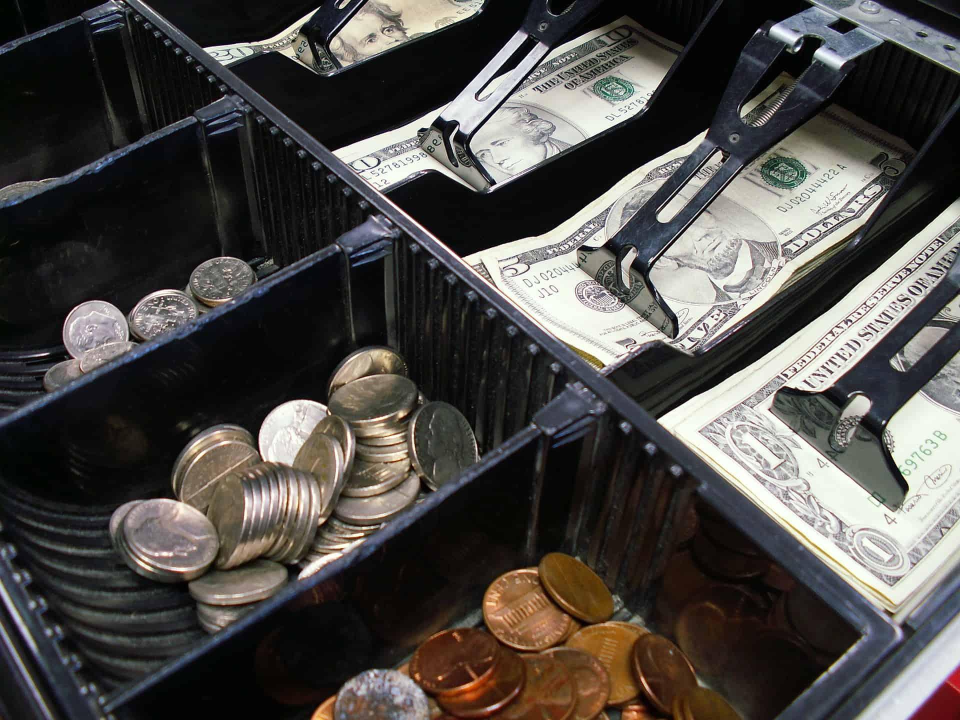 Imagem mostra uma gaveta de dinheiro repleta de notas e moedas de dólares.