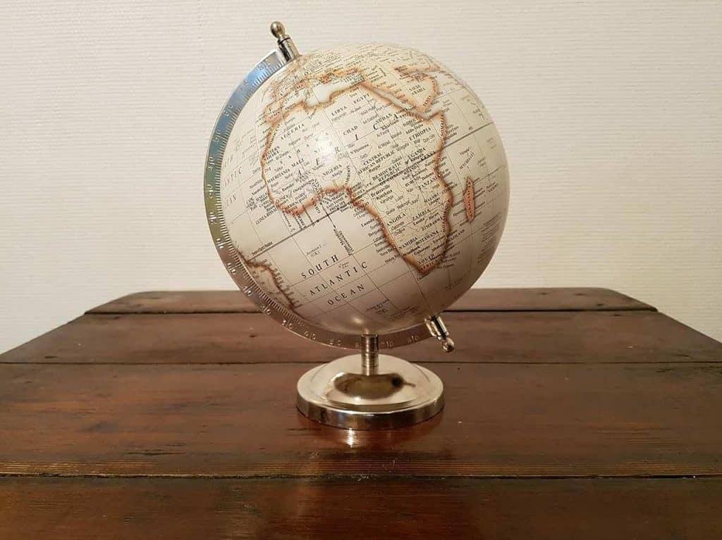 Imagem mostra um globo terrestre sobre uma mesa de madeira.