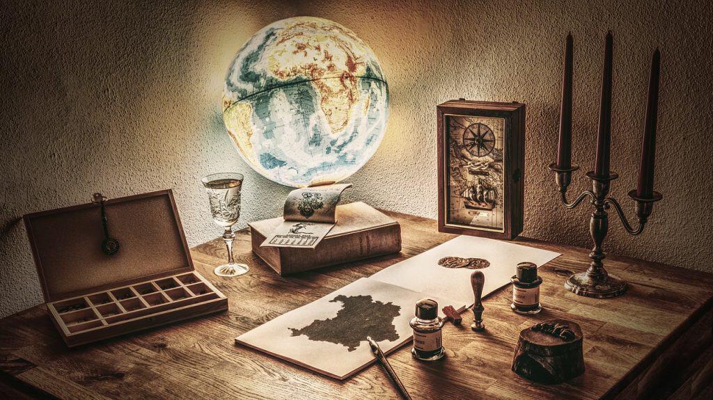 Imagem mostra um globo terrestre iluminado rústico com objetos antigos ao redor em cima de uma mesa.