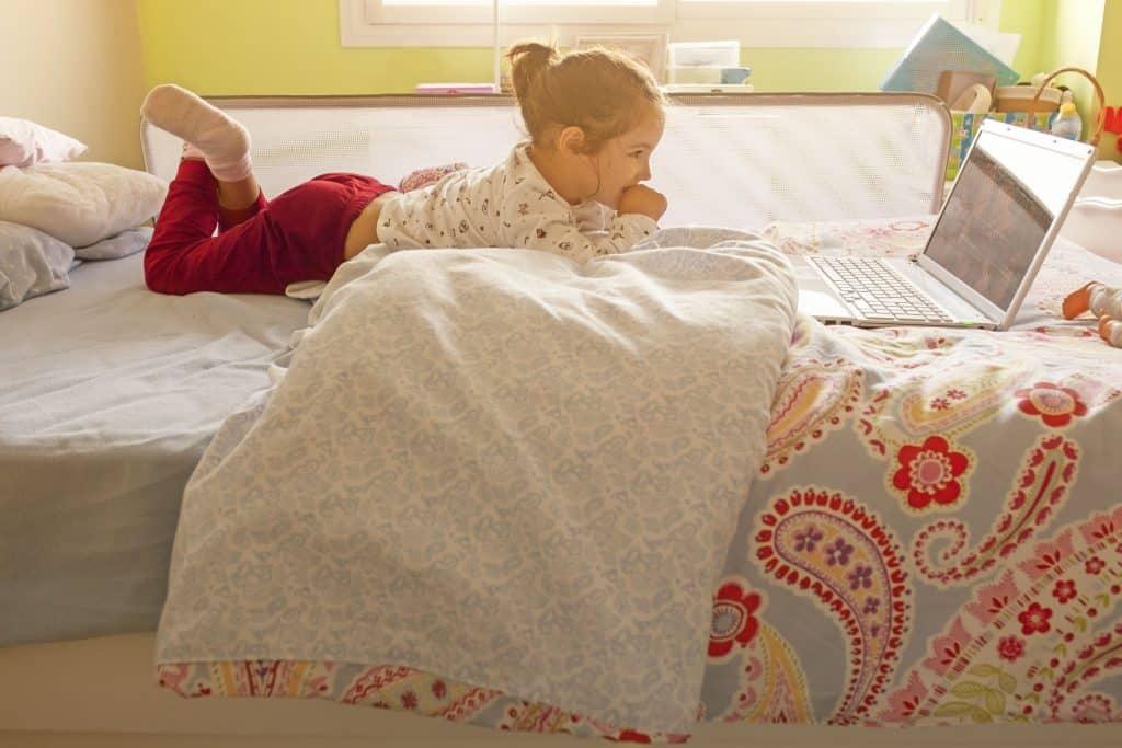 Menina em cama com grade para cama olha para tela de notebook.
