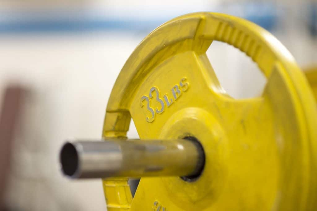 Imagem de anilha amarela de 33 libras em barra de ferro.