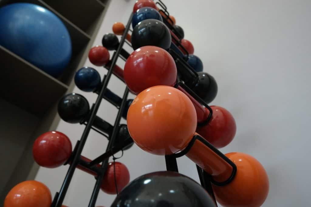 Imagem de suporte com halteres coloridos.