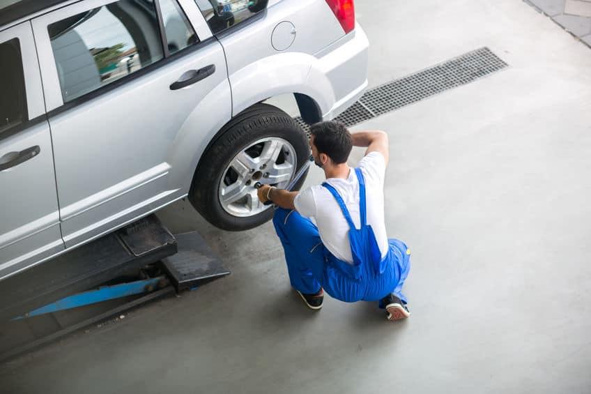 Um homem de macacão azul e camiseta branca que usa uma chave de roda no parafuso de uma roda de carro.