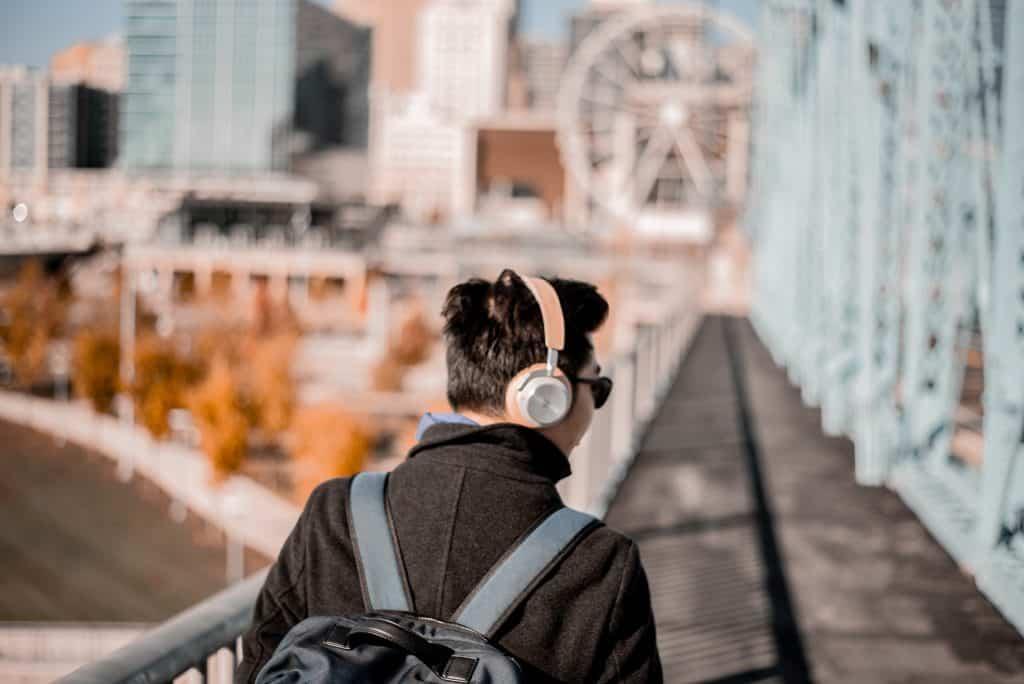Homem de costas, caminhando em uma ponte com fone de ouvido.