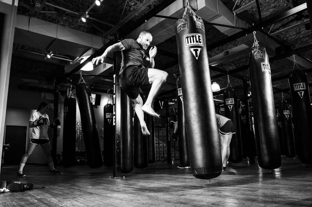 Homem pulando e chutando saco de pancadas em uma academia de luta.