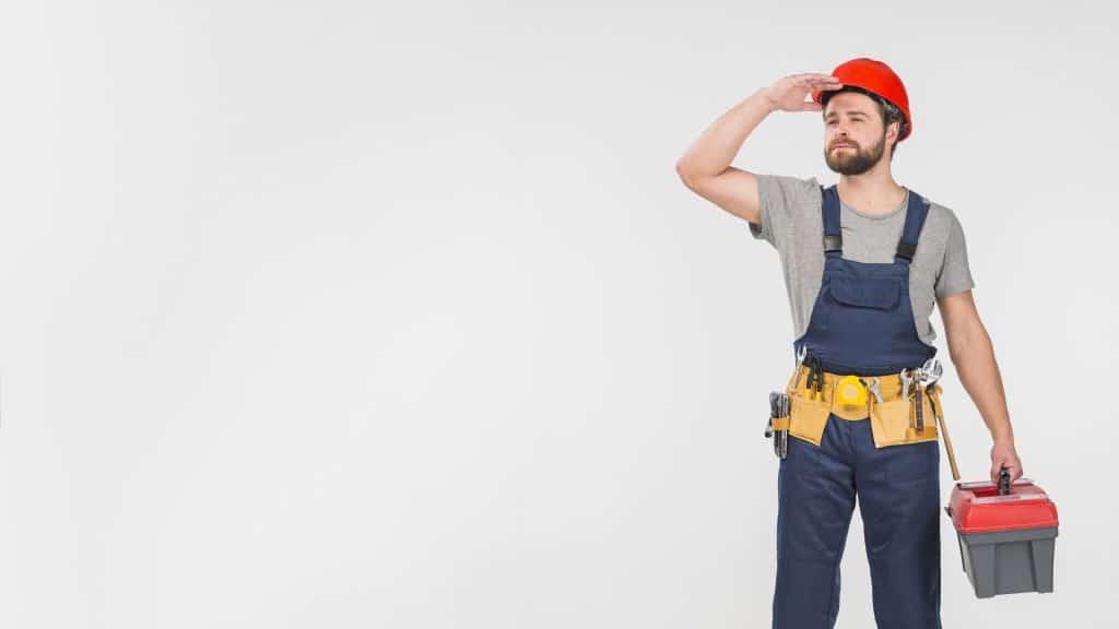 Imagem de um operário com capacete de obra na cabeça e segurando uma caixa de ferramentas.
