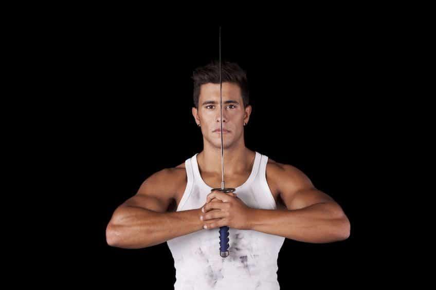 Homem musculoso de regata branca segurando uma espada entre a face.