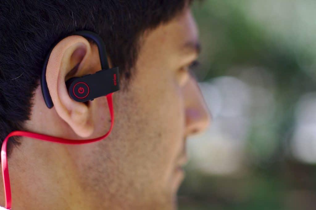 Homem com fone earbud Bluetooth.