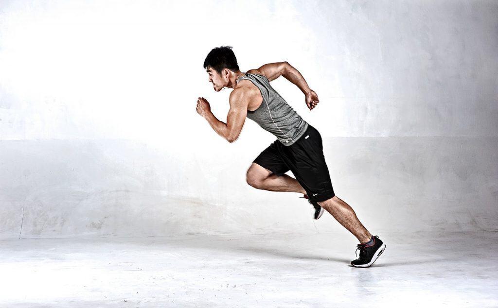 Homem correndo com tênis esportivo em um fundo branco.