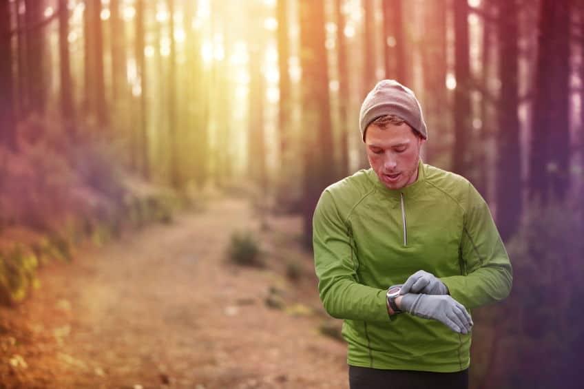 Imagem de homem correndo na natureza e usando relógio com gps.