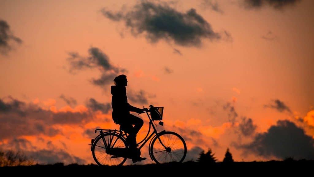 Imagem mostra uma pessoa em uma bicicleta durante o pôr do sol.