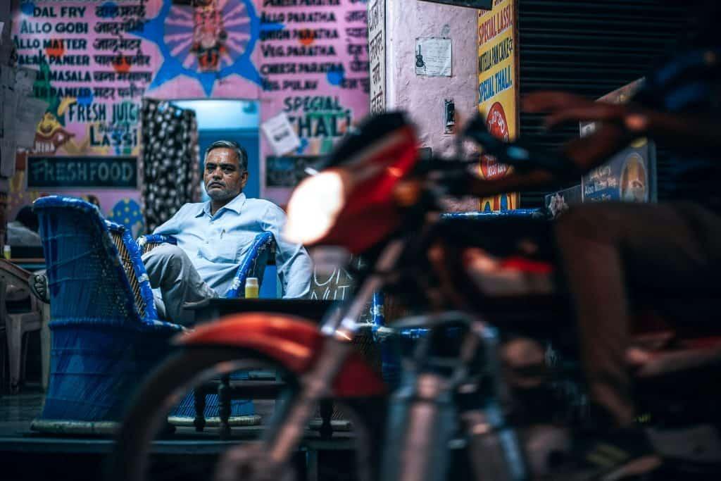 Imagem mostra, ao fundo, um homem sentado num estabelecimento, enquanto observa uma moto na rua, em primeiro plano, desfocada.