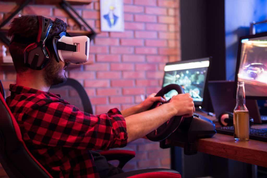 Imagem de homem sentado em cadeira gamer jogando com volante e óculos de realidade virtual.