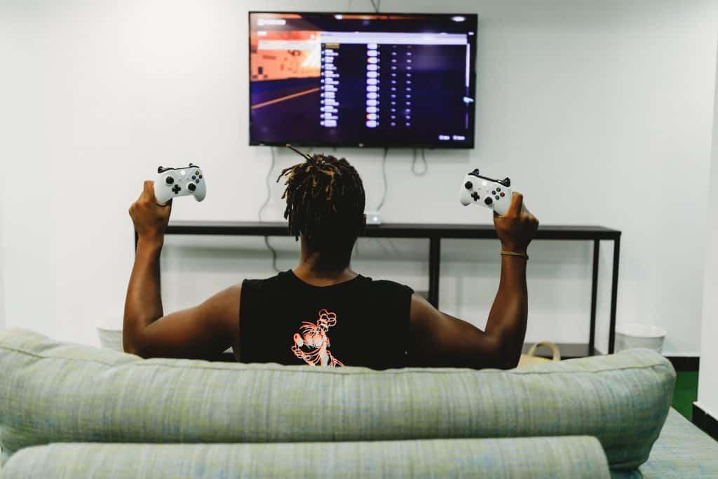 Imagem mostra um homem de costas em frente à uma TV, segurando um controle de Xbox em cada mão.