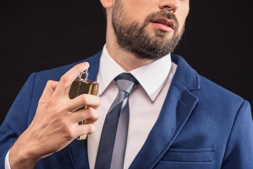 Homem borrifando perfume no pescoço.