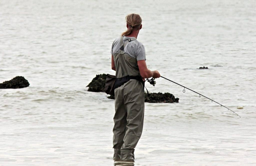 Imagem mostra um homem pescando na beira do mar com uma longa vara.