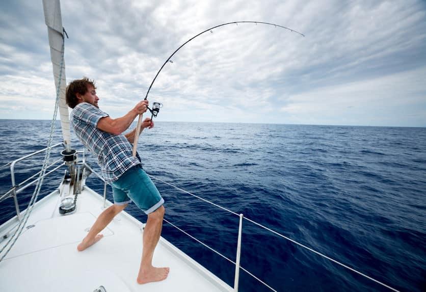 Homem na ponta de um barco fazendo força com uma vara para puxar um peixe do mar.