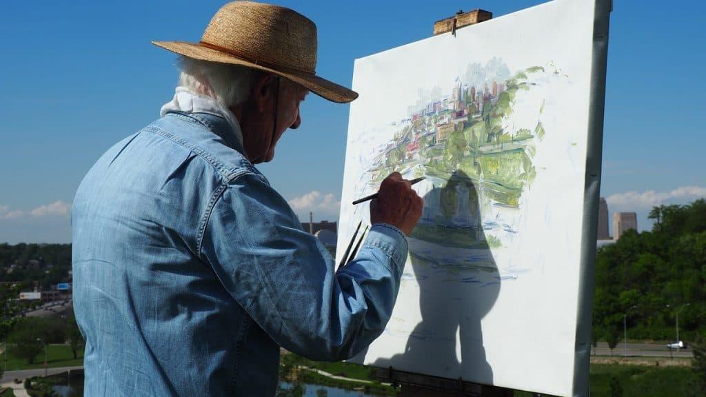 Na foto um senhor pintando uma paisagem em um quadro no meio de um espaço ao ar livre.