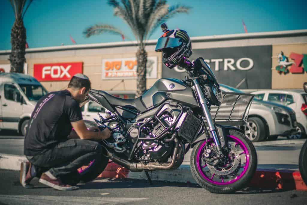 Imagem mostra um rapaz agachado, ajustando a trava da roda traseira de sua moto.