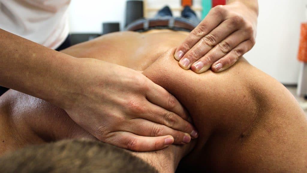 Imagem de homem deitado e recebendo massagem nas costas.
