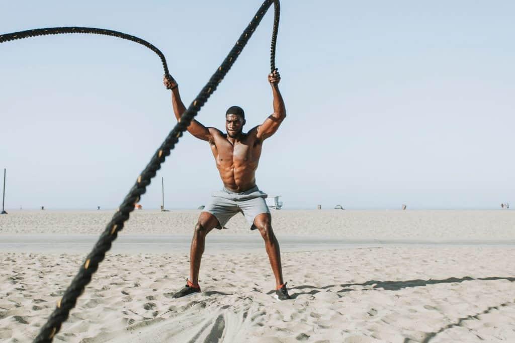 Imagem de homem se exercitando com corda na praia.