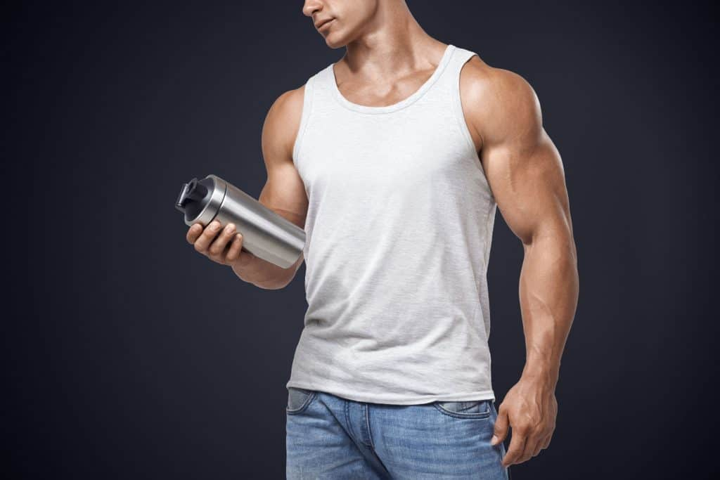 Imagem de homem segurando copo de whey protein.