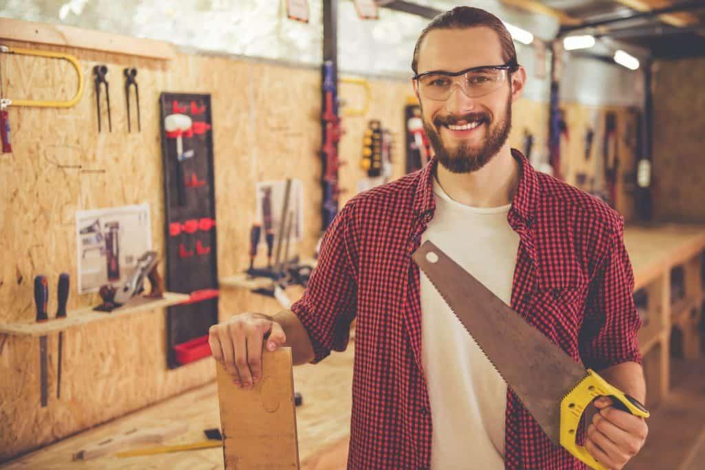 Em uma marcenaria um homem usa óculos de proteção. Ele tem um serrote na mão esquerda e uma tábua de madeira na mão direita.