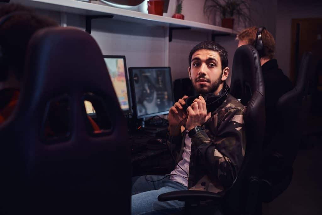 Imagem de homem sentado em cadeira gamer preta.
