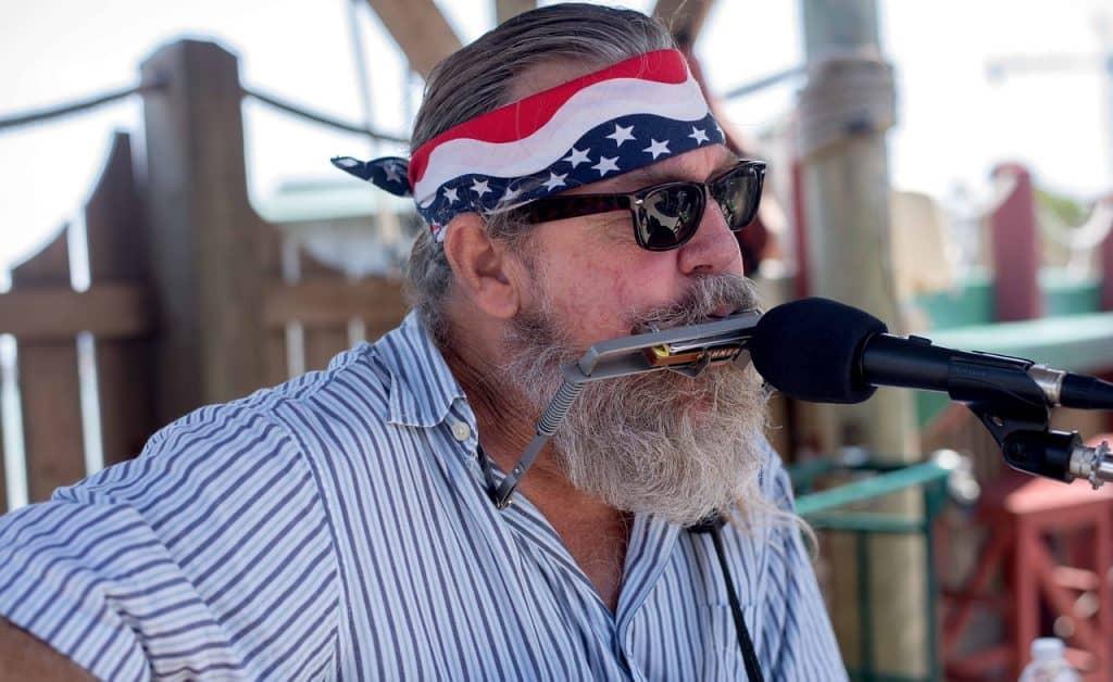 Homem idoso usando camisa, óculos de sol e uma bandana amarrada na testa tocando gaita na frente de um microfone.