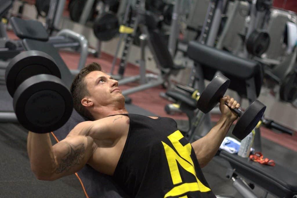 Homem utiliza halteres em um exercício dentro de uma academia de ginástica.