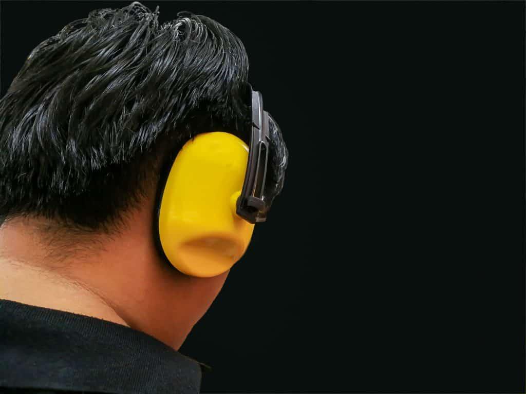 Homem de costas usando abafador de ruído amarelo.
