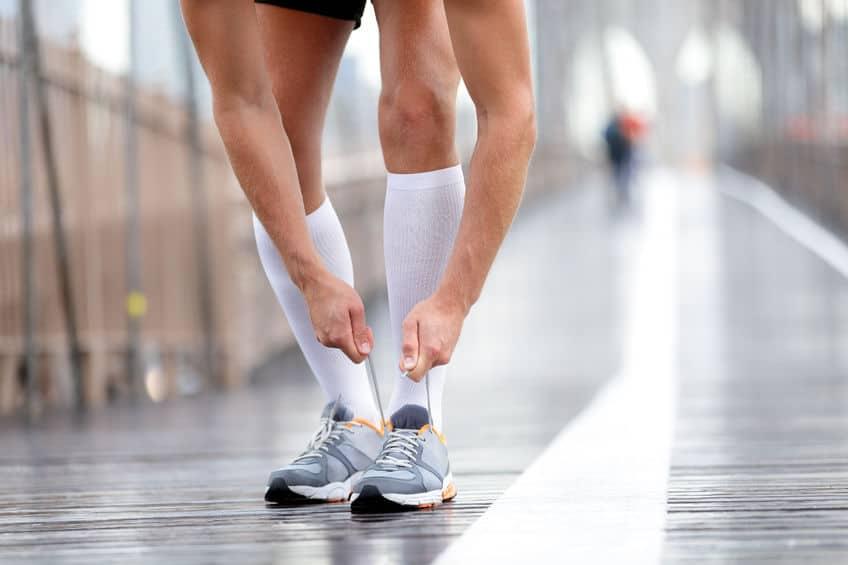 Imagem de pessoa correndo utilizando meia de compressão e tênis.