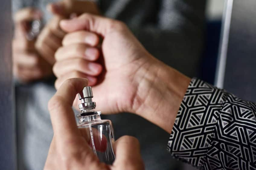 Mãos de homem passando perfume no pulso.