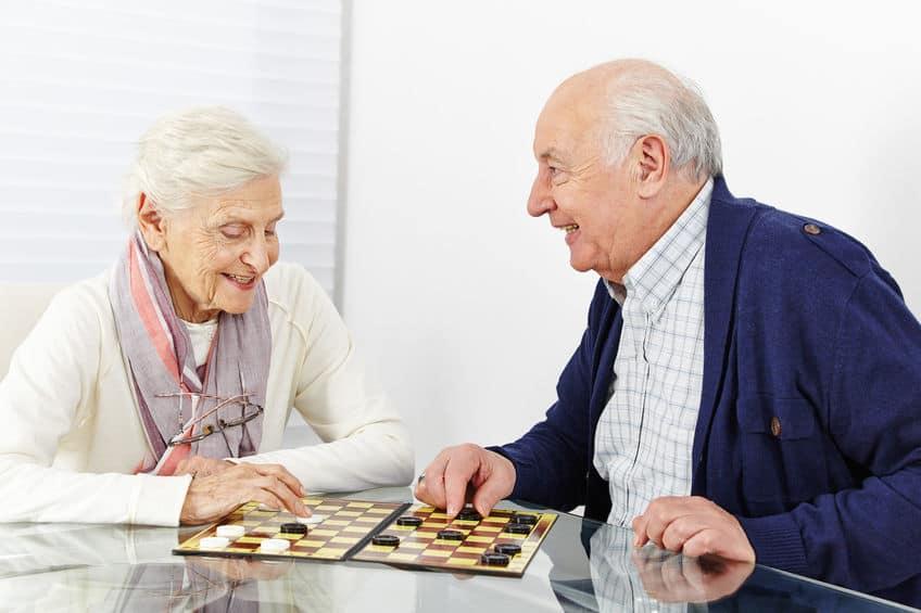 Imagem mostra casal de idosos jogando damas e sorrindo.