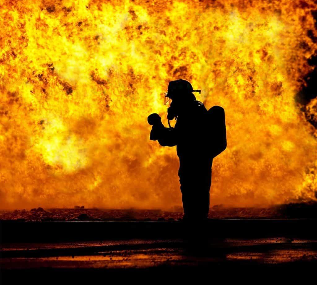 Um bombeiro segura um bebe nas suas mãos. Mais ao fundo, grande incêndio.