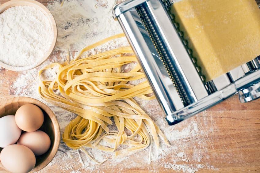 Máquina fazendo macarrão com ingredientes ao lado.