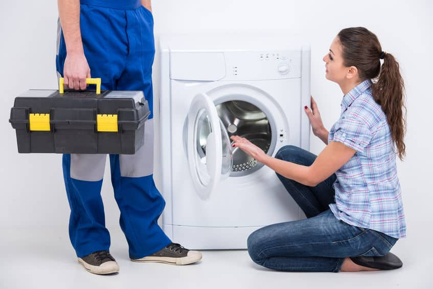Imagem de mulher agachada em frente a máquina de lavar aberta e técnico ao lado.