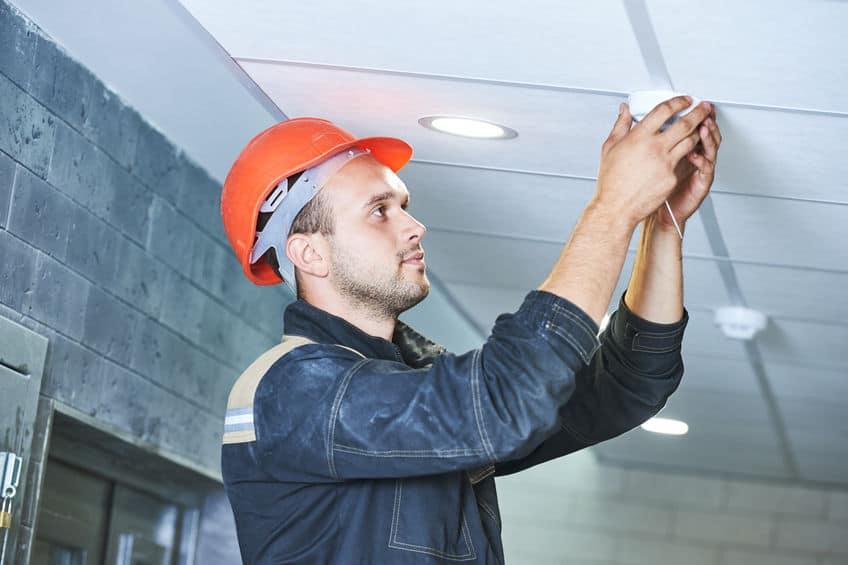 Homem instalando detector de fumaça.